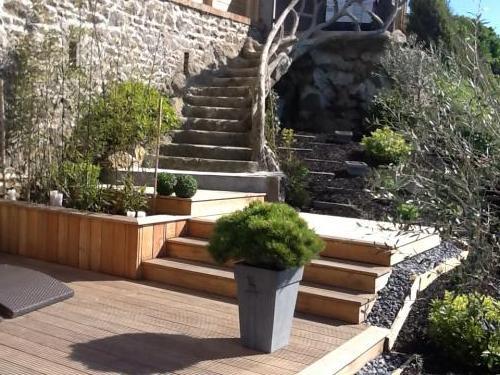 Réalisation d'une terrasse en exotique avec jardinière et escalier intégré.