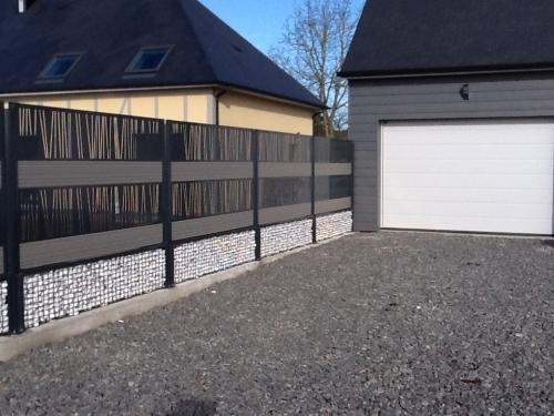 Clôture alu Lookx de chez DIRICKX, avec panneaux alu décor, lames composite et bac deremplissage avec galets.