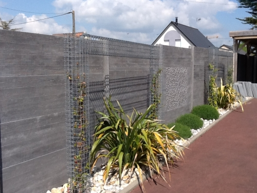 Clôture en panneaux béton avec insertion de motifs au centre, accompagné de quelquesplantations en pied et plantes grimpantes à l'intérieur de gabions