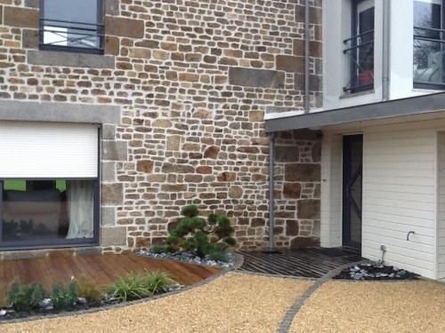 Réalisation d'une cour en gravier beige avec seuil de porte en schiste puis terrasse enCumaru, chainette en pavé granit 'Bleu de Vire'