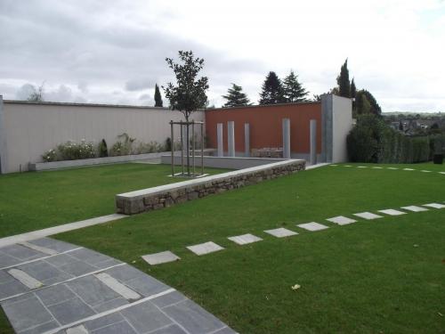 Aménagement de l'espace, avec création d'un muret en pierre, allée en dalle pierrenaturelle, cheminement en pas Japonais, puis gazon.